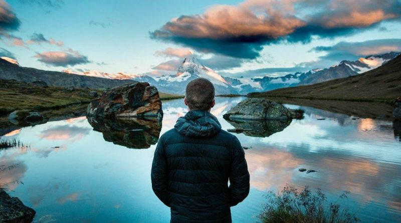 Man standing up in front of lake thinking about what happened